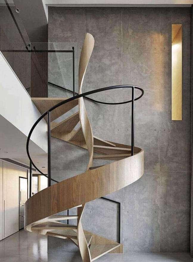 20. Design super moderno para escada caracol de madeira com corrimão de ferro. Fonte: De Lavie Decor