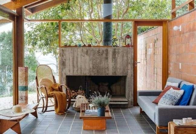 1. Cadeira de balanço para sala rústica decorada com paredes de vidro e lareira – Foto: A V Arquitetura e Engenharia