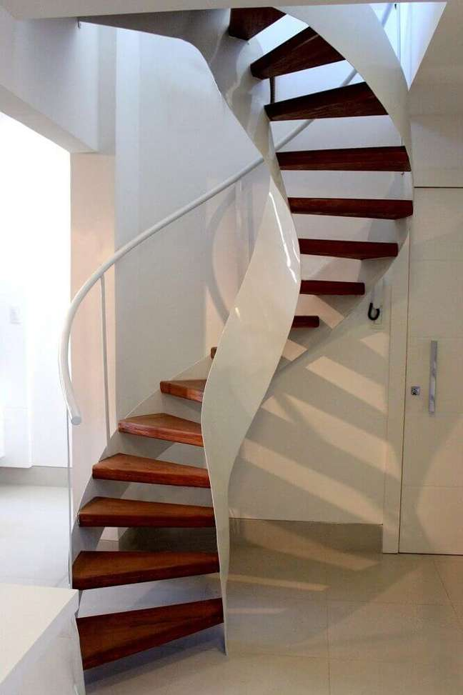 19. Escada caracol de madeira com corrimão branco e design moderno. Fonte: The Ofy