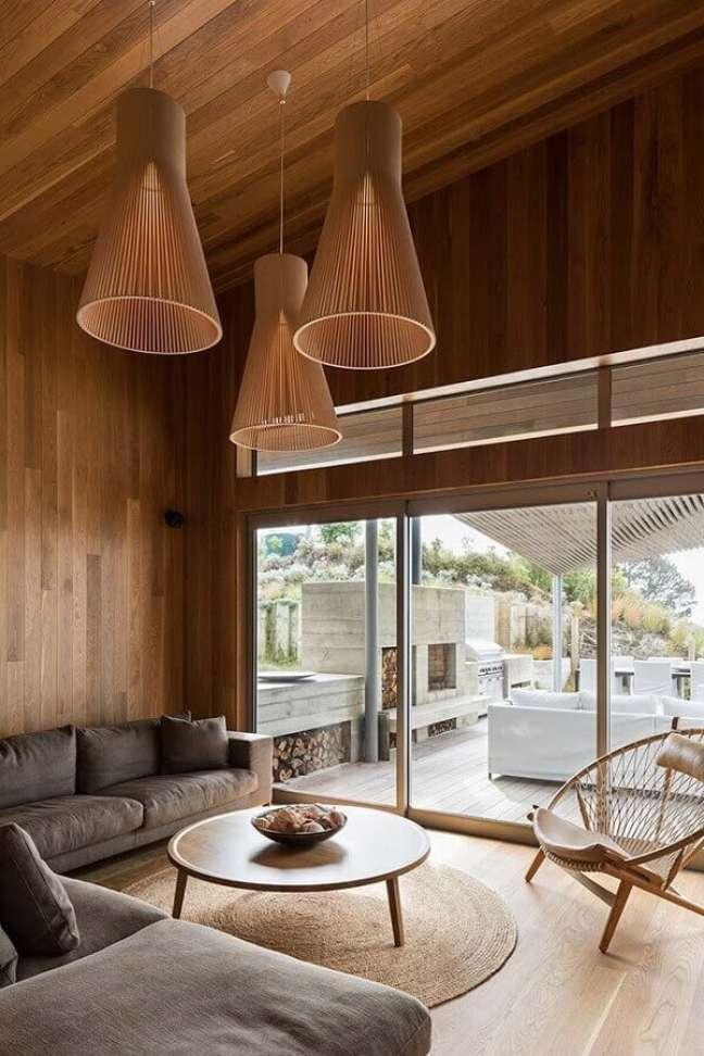 29. Luminária moderna para sala rústica decorada com revestimento de madeira – Foto: Habitus Living