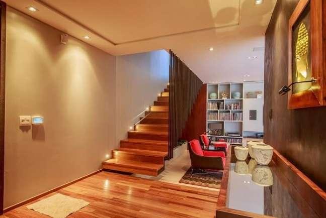 87. O spot de luz embutido traz um toque sofisticado para a escada com degraus de madeira. Fonte: WT Studio