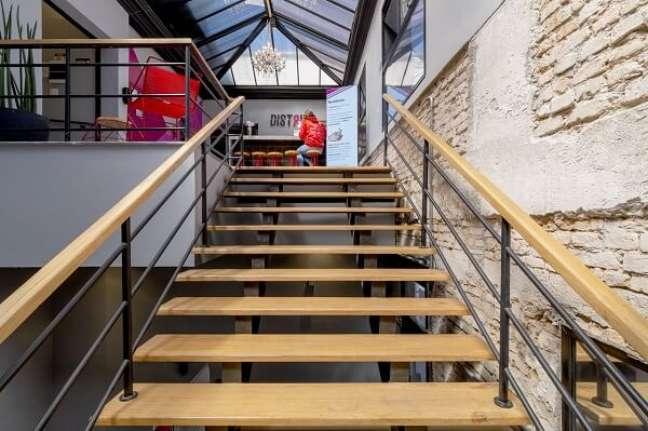 80. Estabelecimento com parede de tijolinho e escada de madeira. Fonte: Aurora Interiores