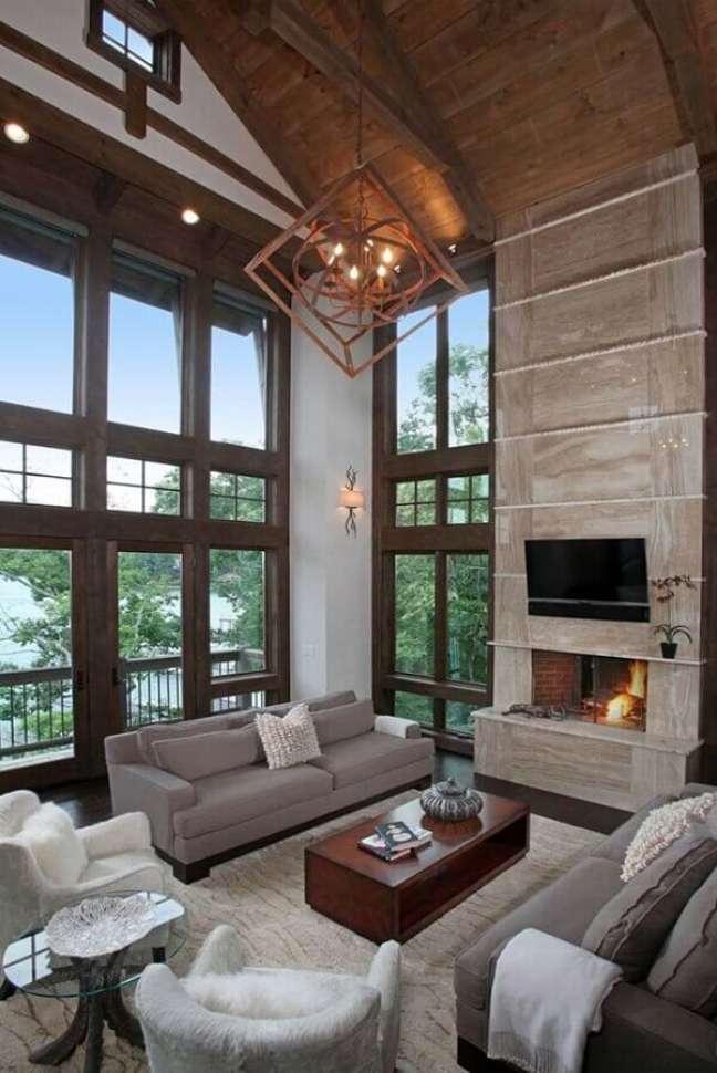 8. Sala de estar rústica decorada com lustre moderno e lareira – Foto: Houzz