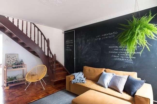 89. Tinta lousa na parede e escada de madeira que dá acesso aos andares superiores. Fonte: INÁ Arquitetura