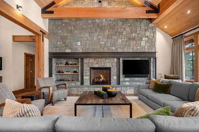 12. Decoração rústica para sala de TV com lareira e revestimento de pedra – Foto: Houzz