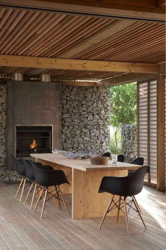 49. Sala de jantar rústica decorada com lareira e revestimento de pedra – Foto: ArchDaily