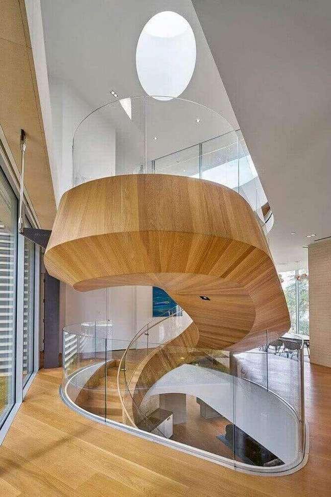 22. Escada caracol de madeira com guarda corpo de vidro levando modernidade e leveza para o ambiente. Fonte: One Kindesign