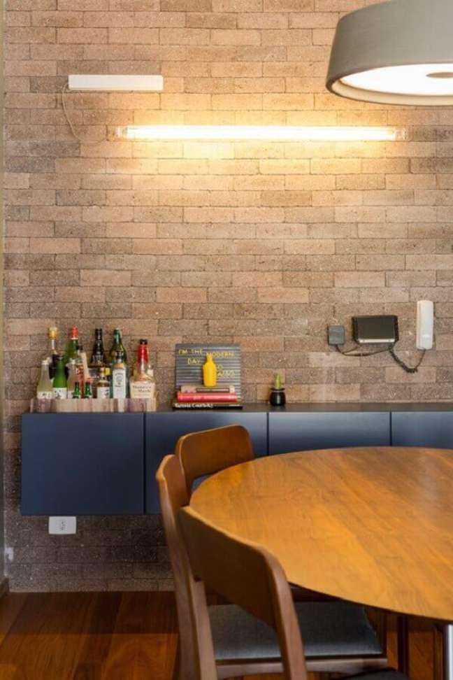44. Parede de tijolinho para decoração de sala de jantar com buffet azul e mesa de madeira – Foto: Design Milk