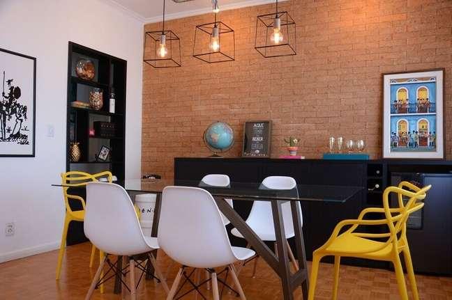 53. Sala de jantar com buffet preto decorada com parede de tijolinho e pendente industrial – Foto: Nathalia Bilibio Schwinn