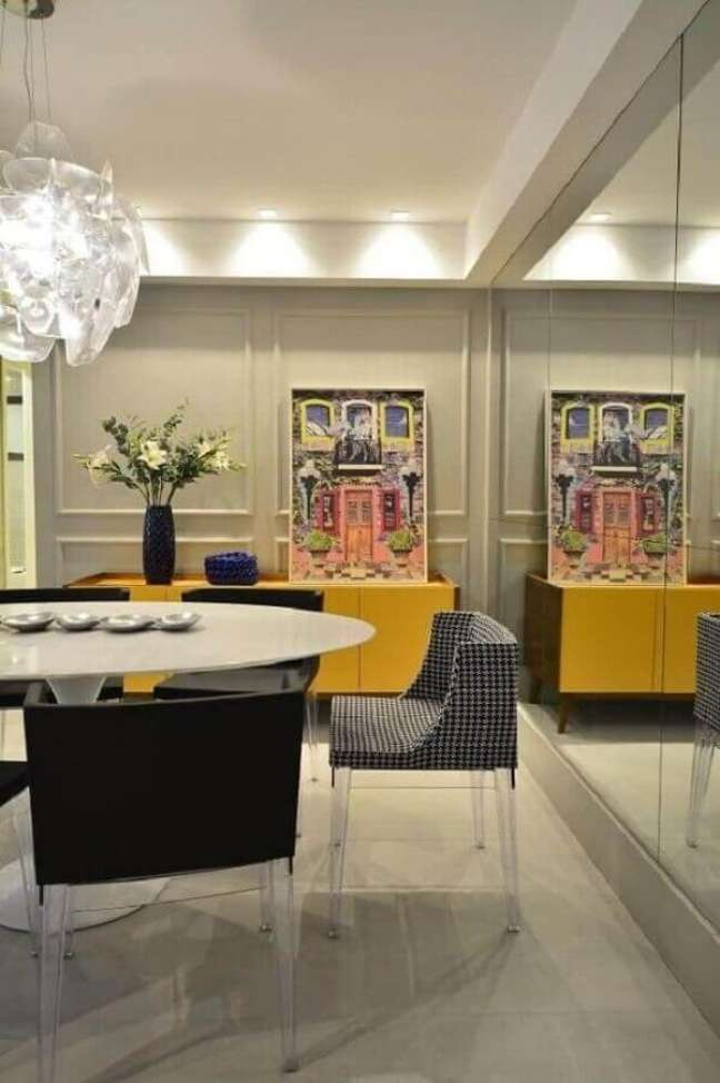 46. Parede espelhada para decoração de sala de jantar com buffet amarelo e cadeira estofada – Foto: BG Arquitetura