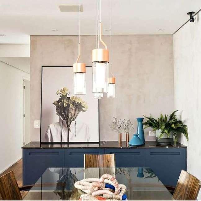 26. Decoração moderna com mesa de vidro para sala de jantar com buffet azul – Foto: Jeito de Casa