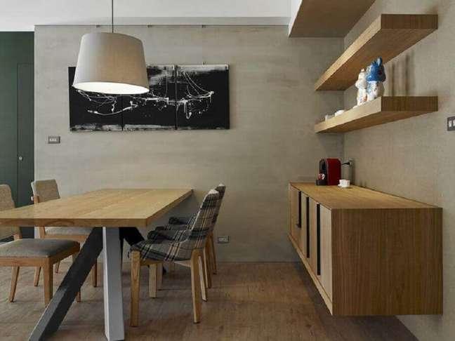 29. Decoração moderna para sala de jantar com buffet de madeira e parede de cimento queimado – Foto: HomeAdore