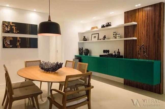 21. Decoração de sala de jantar com buffet suspenso verde e mesa de madeira redonda – Foto: Vitral Arquitetura