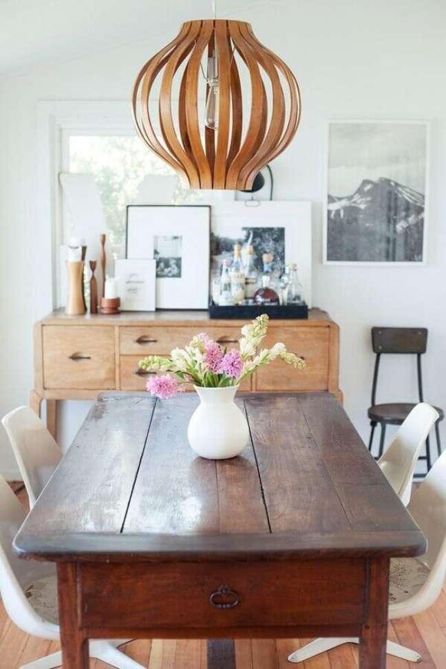32. Decoração simples para sala de jantar pequena com buffet e mesa de madeira – Foto: Refinery29