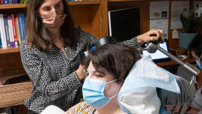 Professora Katherine Scangos verificando dispositivo e progresso de Sarah