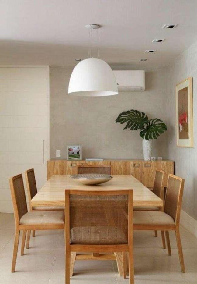 35. Luminária branca para decoração moderna de sala de jantar com buffet de madeira e parede de cimento queimado – Foto: MCA Estúdio