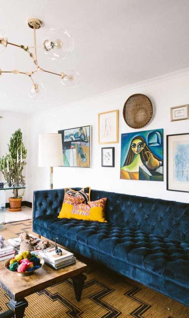 15. Sofá chesterfield azul marinho com almofada amarela – Via: Domino