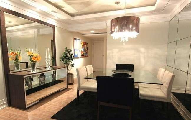 20. Decoração de sala de jantar com buffet espelhado e mesa de vidro – Foto: Decor Salteado
