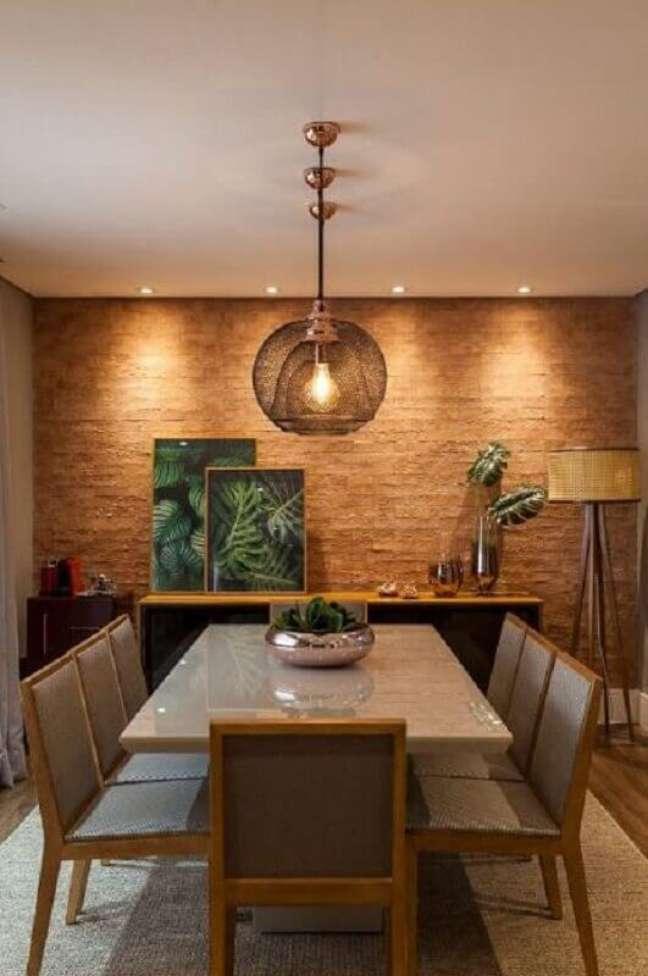 1. Buffet para sala de jantar decorada com abajur de chão e parede rústica – Foto: Jeito de Casa