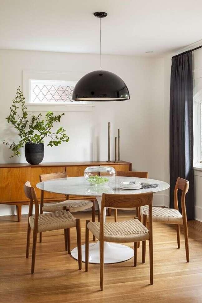 16. Decoração de sala de jantar com buffet de madeira e pendente preto para mesa redonda – Foto: Scout & Nimble