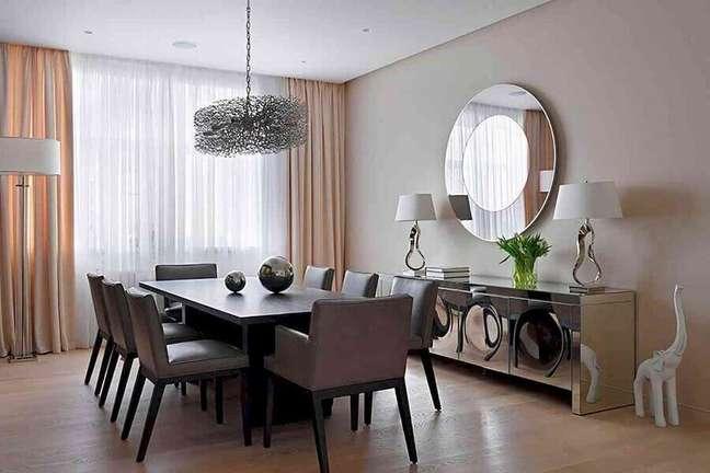 8. Decoração sofisticada para sala de jantar com buffet espelhado e espelho redondo de parede – Foto: Vinh Oanh Glass