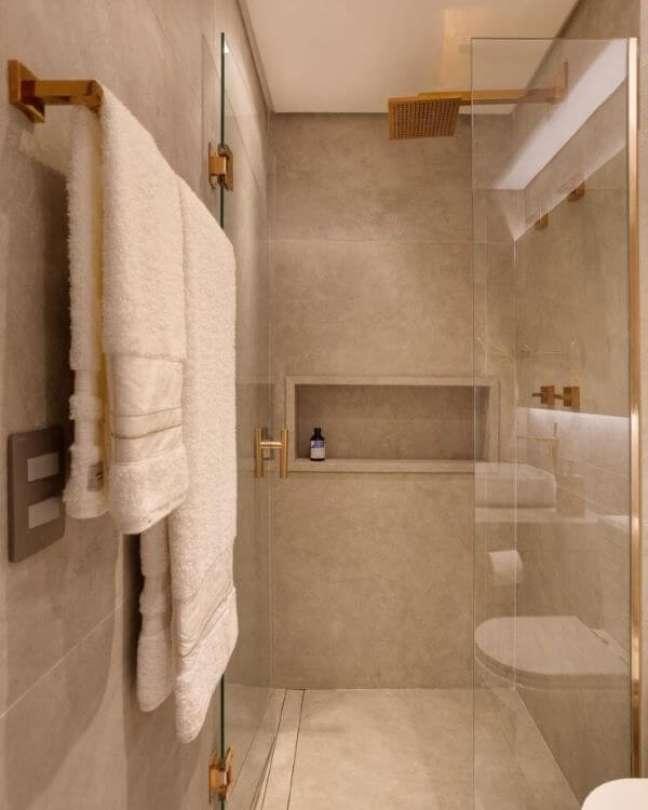 19. Banheiro moderno com nicho de porcelanato e box com detalhes dourados – Foto Studio Ipê