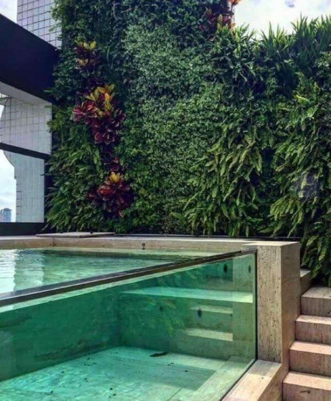 31. Piscina elevada de vidro com decoração de jardim vertical – Foto Elkis Paisagismo