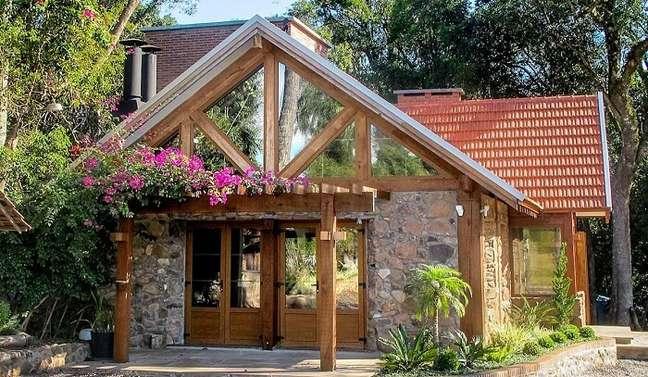 92. Casa simples com parede de pedra e pergolado de madeira. Fonte: Homify