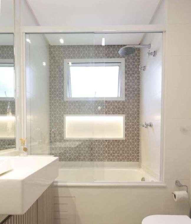 57. Banheiro com banheira e nicho de porcelanato na parede – Foto Daniela Marques