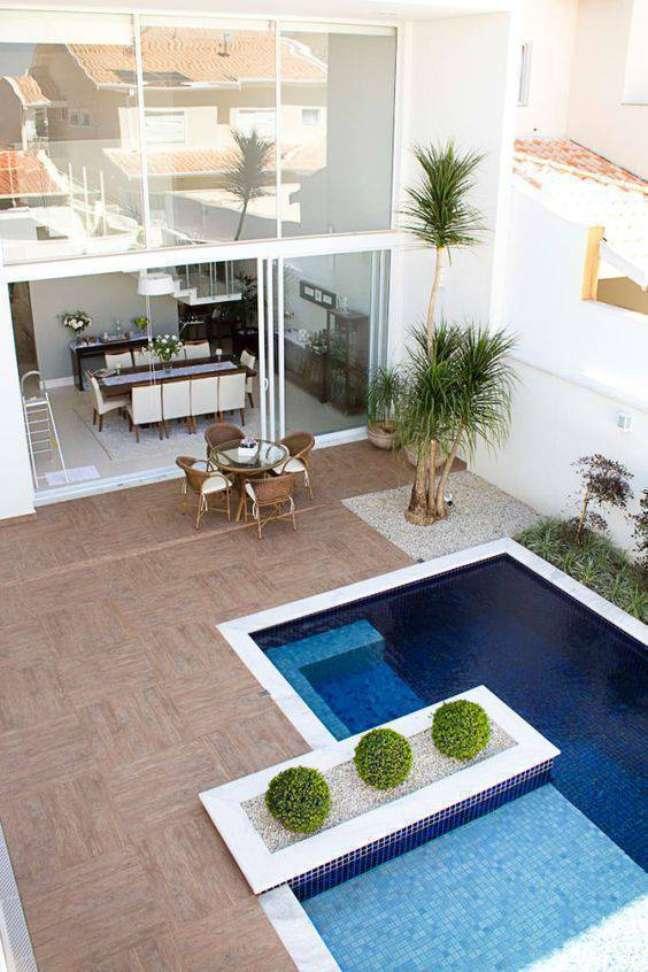 28. Invista na piscina com borda branca e piso antiderrapante para colocar móveis de madeira resistentes – Foto Homify