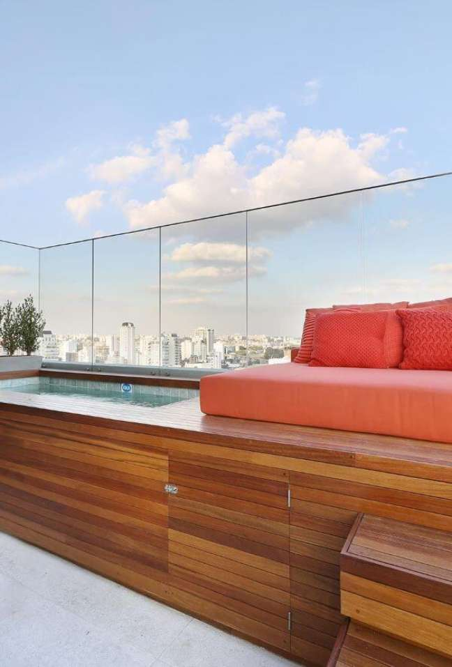 47. Quintal com piscina elevada e deck de madeira com sofá laranja -Foto Casa de Valentina