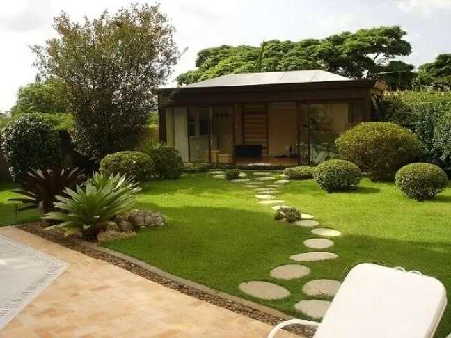96. Casa simples com jardim de pedras que formam um caminho até a casa. Projeto de Alalou Paisagismo