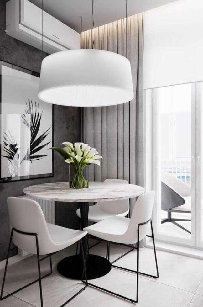 43. Cores de casas modernas para sala de jantar cinza pequena decorada com lustre e mesa redonda – Foto: Mauricio Gebara Arquitetura