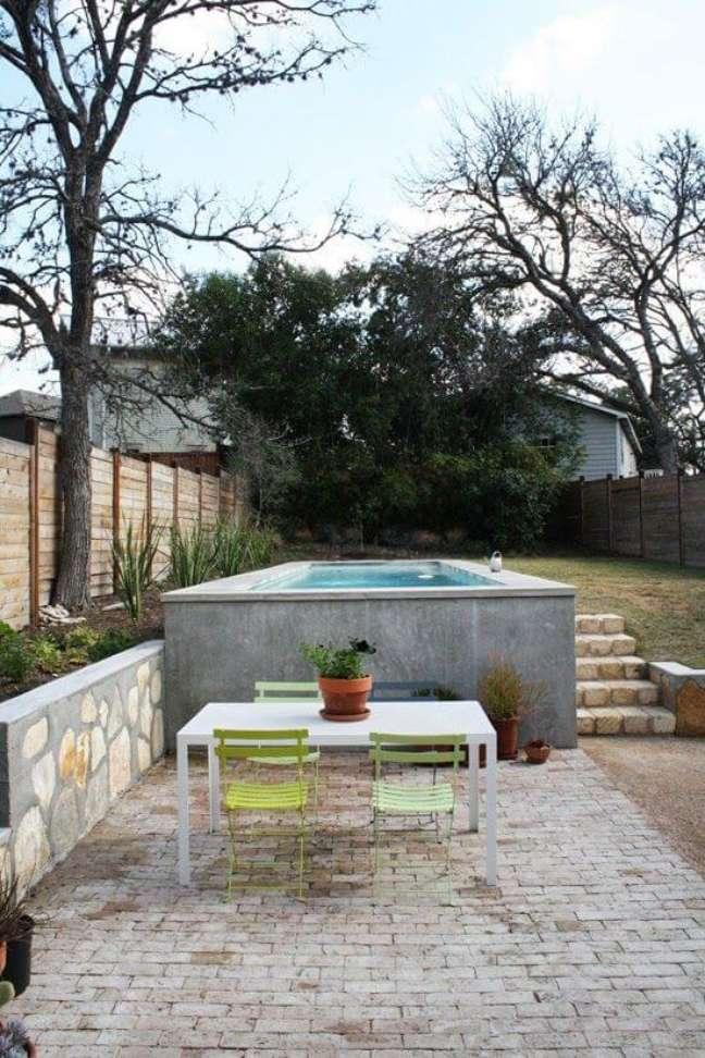 30. Piscina elevada no jardim moderno com mesa para receber amigos bem charmosa – Foto Adrienne Breaux