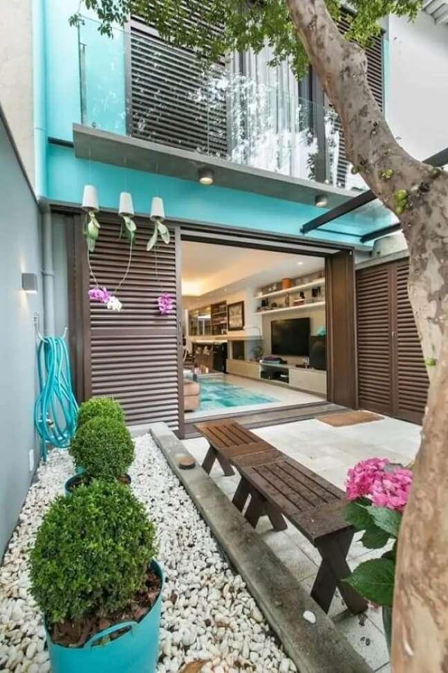 93. Jardim pequeno com pedras brancas, buchinho e orquídeas suspensas trazem alegria para a casa simples. Fonte: DT Estúdio