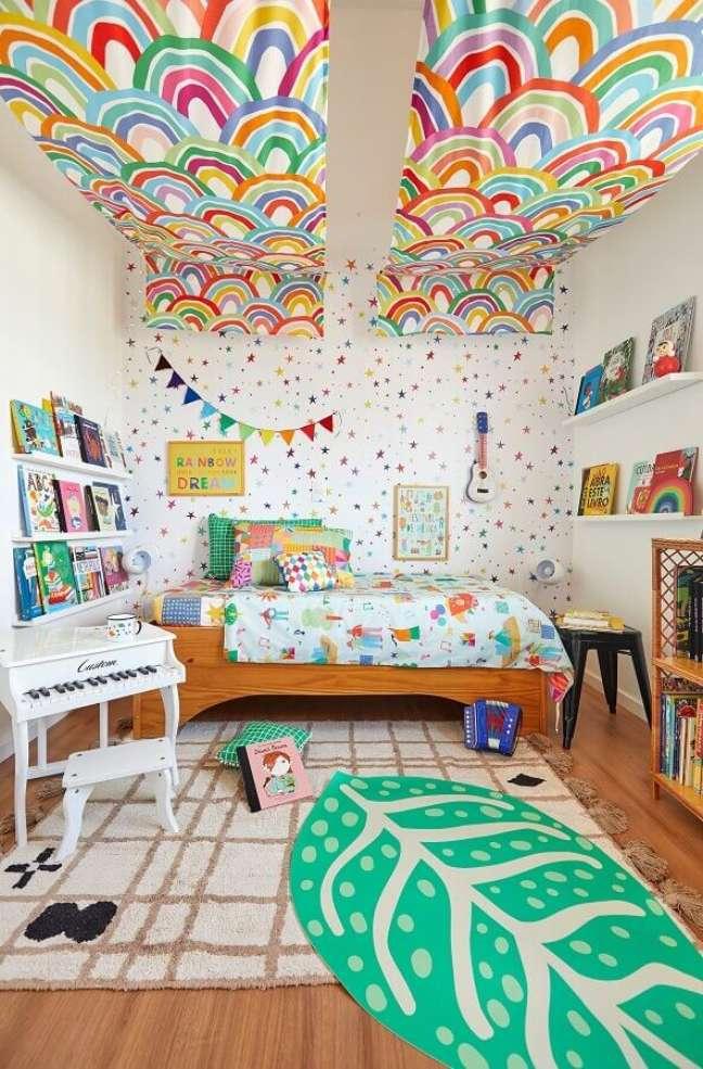 6. Tapete para quarto infantil colorido decorado com prateleiras para livros e cama de madeira – Foto: Marcos Fertonani para MOOUI
