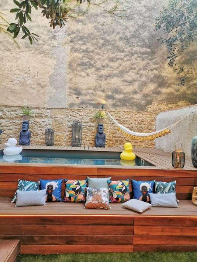 53. Quintal com piscina elevada e deck de madeira e almofadas estampadas – Foto Astuces de Filles