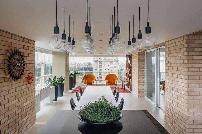 7. Parede de tijolinho e luminária pendente para decoração de varanda de apartamento grande – Foto: FCstudio