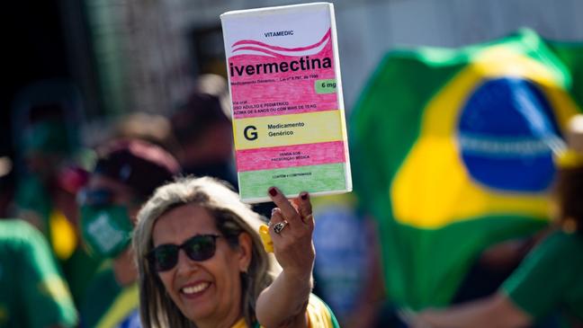 Mulher em manifestação pró-Bolsonaro segura cartaz com desenho de caixa de ivermectina
