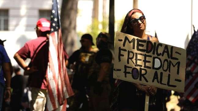 Mulher em protesto antivacina segurando cartaz em que se lê 'liberdade médica para todos'