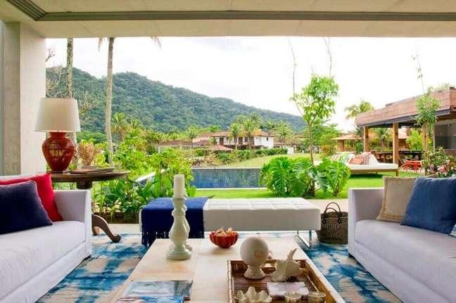 5. Decoração de casa com varanda com tapete azul e branco e almofadas para sofá – Foto: Marília Veiga Interiores