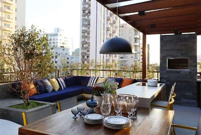 3. Decoração de varanda planejada com sofá de canto e churrasqueira – Foto: Mandril Arquitetura e Interiores