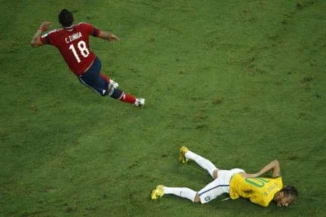 Neymar caído após entrada de Zúñiga (Foto: FABRIZIO BENSCH / AFP)