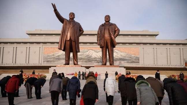 Norte-coreanos se curvam diante das estátuas dos ex-líderes do país, Kim Il-sung e Kim Jong-il