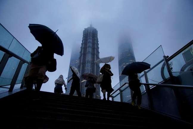 Pedestres seguram guarda-chuvas em Xangai em meio a aproximação do tufão Chanthu 13/09/2021 REUTERS/Aly Song