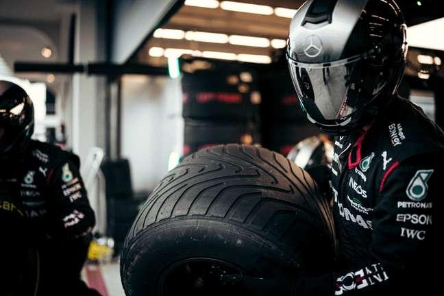 Mecânico da Mercedes carrega pneu intermediário