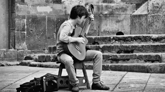 Homem compondo música no violão