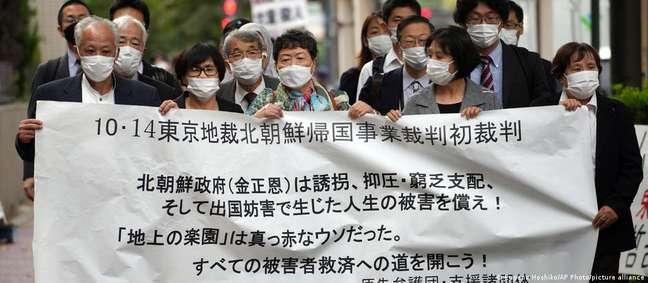 Sobreviventes do programa de repatriação e apoiadores antes do início de audiência em tribunal de Tóquio