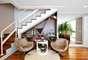 Nesta sala concebida pelas arquitetas do escritório Cavalcante Ferraz Arquitetura e Design, os tons claros e amadeirados presentes na escadaria se espalham pelo cômodo, criando uma harmonia de cores. Informações: (11) 5096-2424
