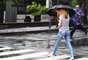 Pedestres se protegem da chuva na região perto do aeroporto de Congonhas, em São Paulo